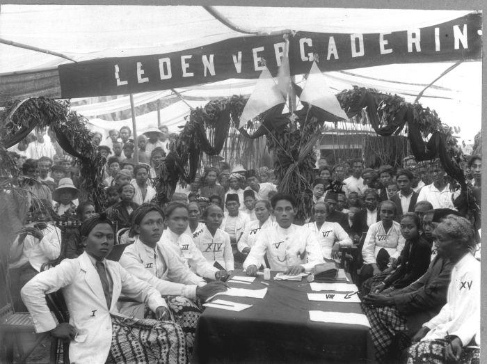 Foto. Groepsportret tijdens een ledenvergadering van de Sarekat Islam (SI) in Kaliwoengoe. Aanwezig zijn leden van de Sarekat Islam afdelingen in Kaliwoengoe, Peterongan en Mlaten (beide in Semarang), alsmede leden van de Vereeniging van Spoor- en Tramwegpersoneel (VSTP) in Semarang.. Groepsportret tijdens een ledenvergadering van de Sarekat Islam (SI) in Kaliwoengoe